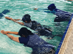 Three multicultural women in the pool with faces in the water as part of their swimming lesson