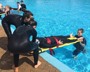 Lifeguards at Adventure World practising spinal board techniques in the pool