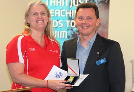 Angela Carey receiving her award from RLSSWA President Ross Peters