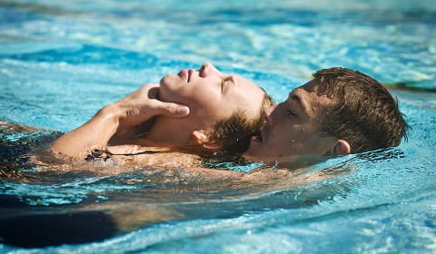 young man performing aquatic rescue of female swimmer