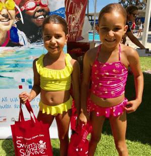 Two little girls in their bathers holding red Swim & Survive Open Day bags