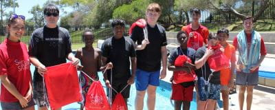 Swim instructors and students by the pool with their Swim and Survive bags