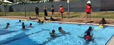 Aboriginal children in the water with others along the edge holding pools noodles to rescue them, instructors looking on