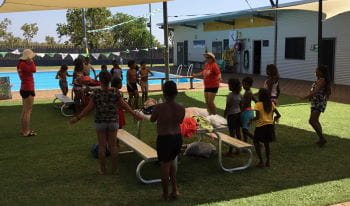Aboriginal children standing on the grass by the pool learning skills from their two instructors