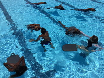 Aboriginal children floating on their back in the pool holding kickboards
