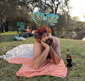 A man dressed as a mermaid laying on a blanket by the river