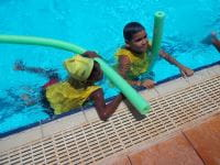 Two children in the pool with noodles