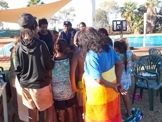 family and friends gathering by the Yandeyarra pool to sing happy birthday to Elijah
