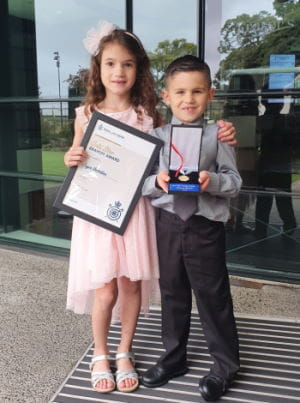 Jayce with his cousin Kortney holding his Bravery Award at Kings Park