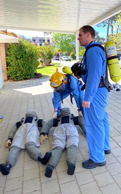 Two people wearing breathing apparatuses carrying rescue manikins