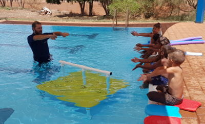 Instructor Aaron Jacobs in the pool with aboriginal children along the edge during their swimming lessons