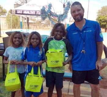 Pool Manager Aaron Jacobs with three aboriginal children holding Swim for Fruit prize bags