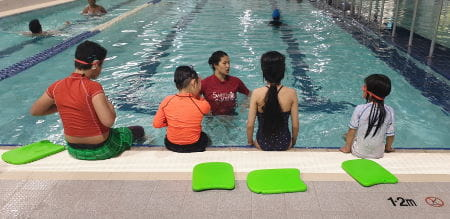 Four children sitting along the edge of a pool facing their instructor in the water