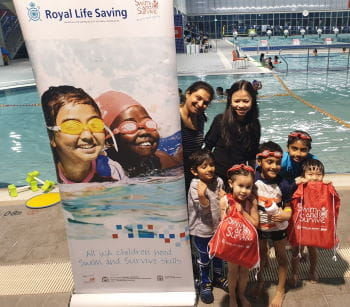 Two mums with their children in bathers with Swim and Survive bags, standing beside a Swim and Survive Access and Equity sign by the pool at Cannington