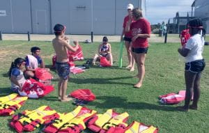 Children with their swim instructors learning about lifejackets at Champion Lakes