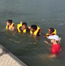 Children wearing lifejackets in the water at Champion Lakes