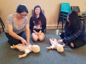 3 Chinese women practising CPR on infant manikins