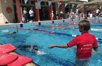A swim instructor in the water at Churchlands with a student practising backstroke