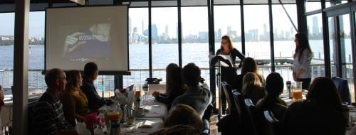 Image of community trainers sitting at table looking out on the Swan River at The Boat Shed