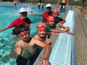 Two swim instructors in the water with multicultural children at Lynwood Senior High School