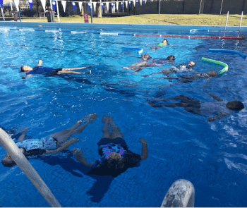 Children floating on their back in the pool at Coolgardie