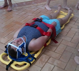 image of a patient strapped to a spinal board by the side of a pool