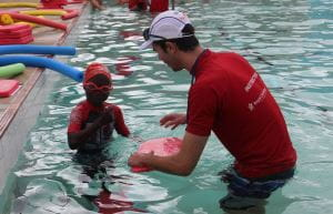A boy smiling at the camera with his swim instructor