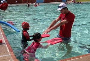 Two children with their swim instructor in the pool at Dianella