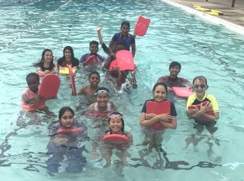 A group of multicultural children in the pool holding kickboards