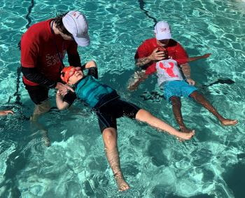 Two swim instructors with two children learning to float on their backs