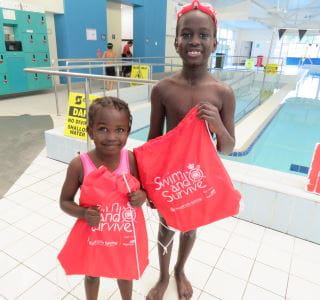 a girl and boy holding their swim and survive packs by the pool at Balga