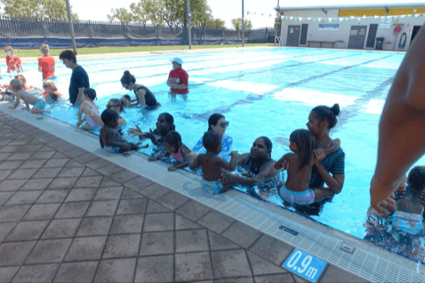 Group of Aboriginal women and their babies in a swimming pool at Fitzroy Crossing