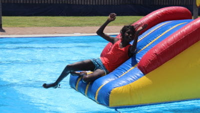An aboriginal boy sliding off the pool inflatable at Fitzroy