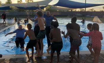 Children pushing police officers into the Fitzroy Crossing Remote Pool