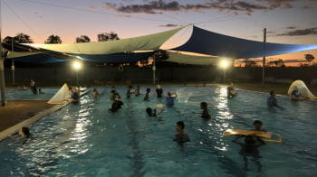 Community Members swimming in the pool at Fitzroy Crossing with the sun setting in the background