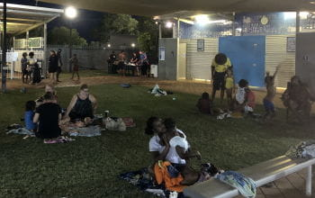 Familiess gathering on the grassed area by the Fitzroy Crossing pool at night time