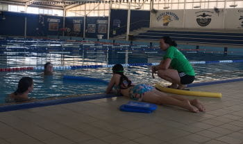 Girls from Geraldton girls academy in the pool while one lays on the edge to rescue them, with an instructor nearby