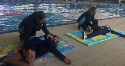 Two students from Geraldton Girls Academy leaning over other students practising first aid skills