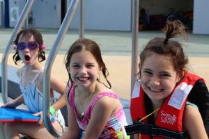 Three girls sitting along the edge of the pool at Geraldton Aquarena