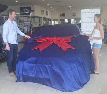 Raffle winner Dean English and daughter Carrie with their car under a blue cover with a red bow
