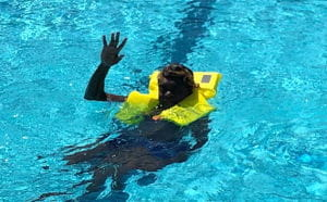 young aboriginal man wearing a lifejacket in a pool