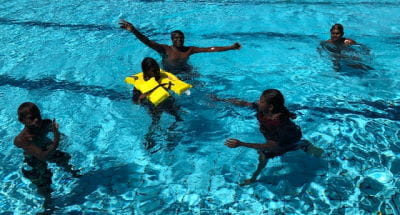 Aboriginal participants in the water while one wears a lifejacket