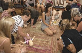 A group of women practising infant CPR