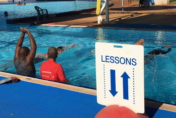 Multicultural men in the pool learning swimming skills with their swim instructor