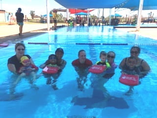 group of parents and toddlers enjoying an Infant Aquatics lesson with an instructor in the pool at Hedland