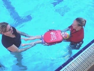 image of a parent and swim instructor assisting a toddler to float on her back with a swim and survive kickboard