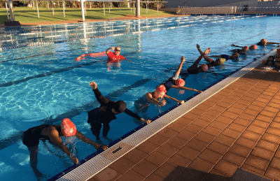 Women lined up along the edge of the pool practising their freestyle breathing while their swim instructor stands behind them in the water
