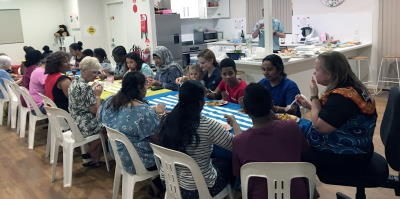 Women and their families enjoying a meal after completing their swimming lessons