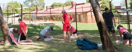 A group of people practising CPR skills on the grassed area by the pool at Hollywood Primary