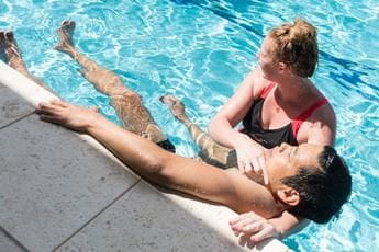 A woman holding a man up along the edge of a pool while practising rescue